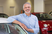 Smiling customer leaning on car — Stock Photo