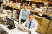 Warehouse managers working together on laptop — Stock Photo