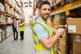 Warehouse worker scanning box while smiling at camera — Stock Photo