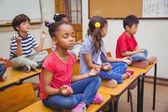 Pupils meditating in lotus position on desk in classroom — Foto Stock