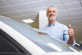 Smiling customer giving thumbs up — Stock Photo