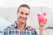 Smiling man showing pink piggy bank — Stock Photo