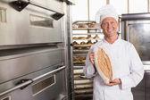 Baker showing freshly baked loaf — Stock Photo