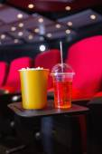 Empty rows of red seats with pop corn and drink on the floor — Stock Photo