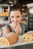Pretty brunette looking at swiss roll — Stock Photo