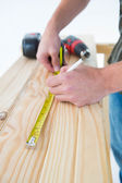 Carpenter with measure tape marking on plank — Stock Photo