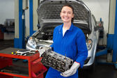 Mechanic holding an engine and smiling — Stock Photo
