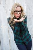 Blonde in striped shirt blowing a kiss — Stock Photo