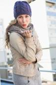 Blonde in warm clothes blowing kiss — Stock Photo