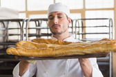 Baker smelling freshly baked baguettes — Stock Photo