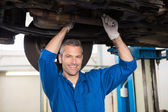 Mechanic smiling at the camera under car — Photo