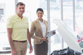 Businesswoman and customer looking at car engine — Stock Photo