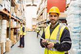 Smiling worker wearing yellow vest using handheld — Stock Photo
