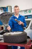 Smiling mechanic inflating the tire — Foto de Stock