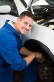 Smiling mechanic adjusting the wheel — Stock Photo