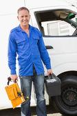 Handyman smiling holding toolbox — Stock Photo