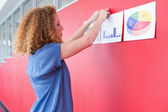 Student hungs paper on the wall — Stock Photo
