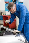 Mechanic checking the oil of car — Stock Photo