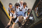 Cute schoolchildren getting on school bus — Fotografia Stock