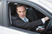 Unsmiling businessman in the drivers seat — Stock Photo