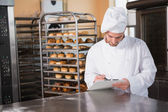 Focused baker writing on clipboard — Stock Photo