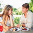 Couple having champagne and desert in the park — Stock Photo #68907771