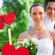 Bride and groom in garden against hearts — Stock Photo #68908765