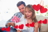 Couple with flowers and greeting card against hearts — Stock Photo