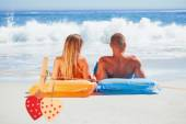 Couple in swimsuit sunbathing together against hearts — Stock Photo