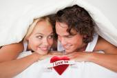 Couple under a duvet with a knowing smile — Stock Photo