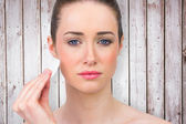 Beautiful brunette using powder puff — Stock Photo
