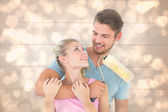 Couple hugging and holding paint roller — Stock Photo