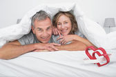 Couple under the duvet against linking hearts — Stock Photo