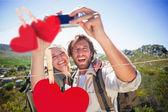 Couple standing on mountain terrain taking a selfie — Stock Photo