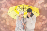 Couple in winter fashion sneezing under umbrella — Stock Photo