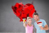 Couple smiling and holding paintbrushes — Stock Photo
