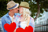 Couple kissing by railings against hearts — Stock Photo