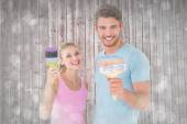 Couple smiling and holding paintbrushes — Stock Photo