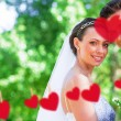 Bride and groom in garden against hearts — Stock Photo #68910929