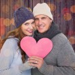 Couple in warm clothing holding heart — Stock Photo #68911255