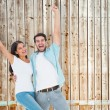 Couple cheering together against faded pine — Stock Photo #68912443