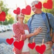 Couple hugging in the city against hearts — Stock Photo #68912607