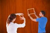 Couple deciding to hang picture — Stock Photo