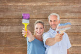 Happy couple holding paintbrushes — Stock Photo
