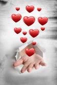 Hand bursting through paper against hearts — Stock Photo