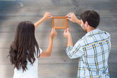 Couple putting up picture frame — Stock Photo