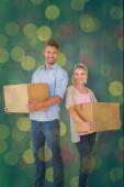 Young couple carrying moving boxes — Stock Photo