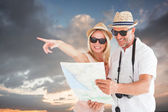 Couple using map and pointing against blue — Stock Photo