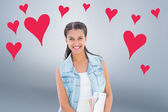 Student holding notepads against hearts — Stock Photo