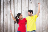 Couple cheering in red and yellow tshirts — Stock Photo